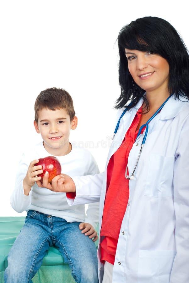 Lächelnder Doktor, der einem Kind Apfel gibt stockbilder