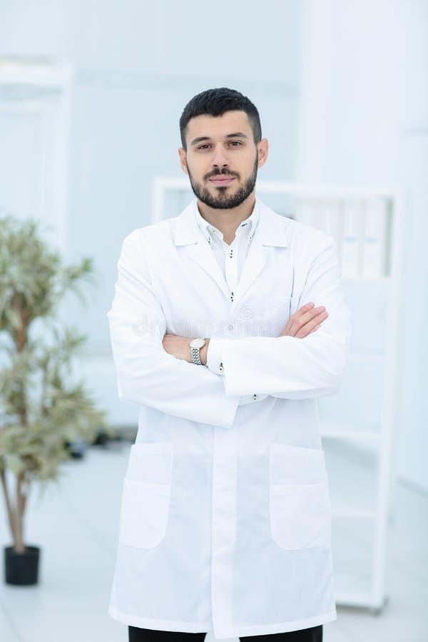 Lächelnder Doktor, der mit den Armen gekreuzt werden im Büro aufwirft, trägt er ein medizinisches Personal auf dem Hintergrund stockbilder