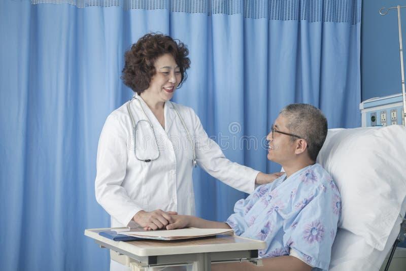 Lächelnder Doktor, der oben auf einem Patienten sich hinlegt in einem Krankenhausbett überprüft stockfotos