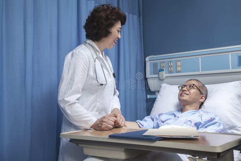 Lächelnder Doktor, der oben auf einem Patienten sich hinlegt in einem Krankenhausbett, Händchenhalten überprüft stockbild