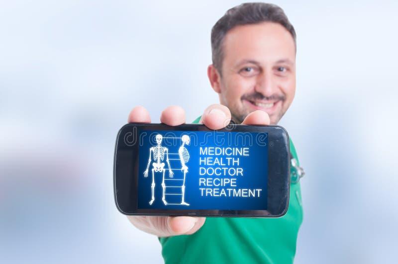 Lächelnder Doktor, der sein Mobiltelefon mit medizinischer Schnittstelle hält stockfoto