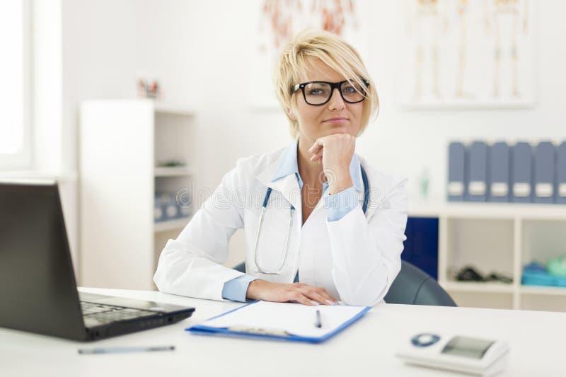 Lächelnder Doktor in ihrem Büro lizenzfreie stockbilder