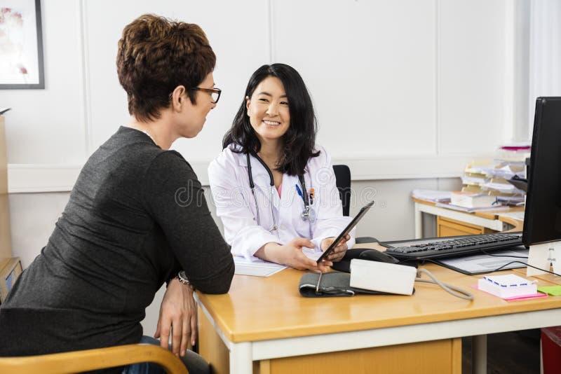 Lächelnder Doktor Showing Digital Tablet zum Patienten lizenzfreie stockfotografie
