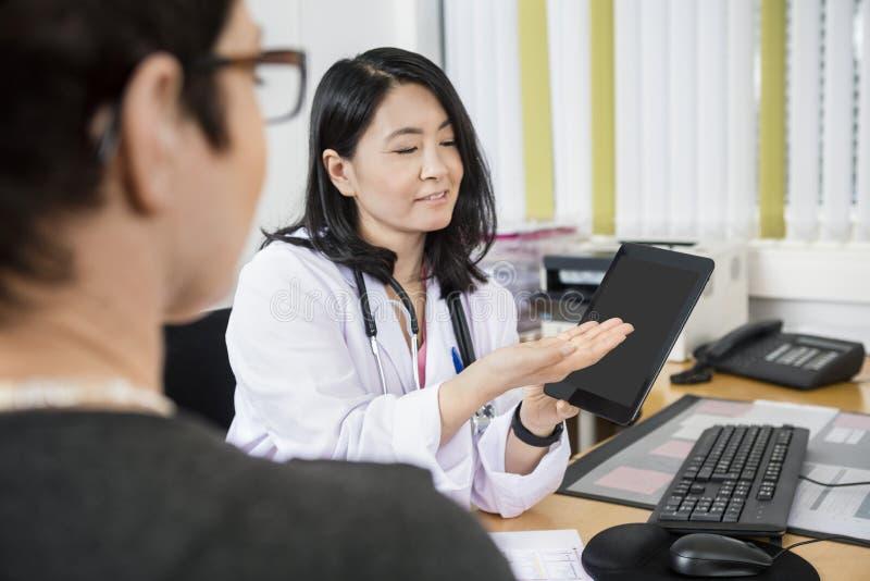 Lächelnder Doktor Showing Tablet Computer zum Patienten lizenzfreies stockfoto