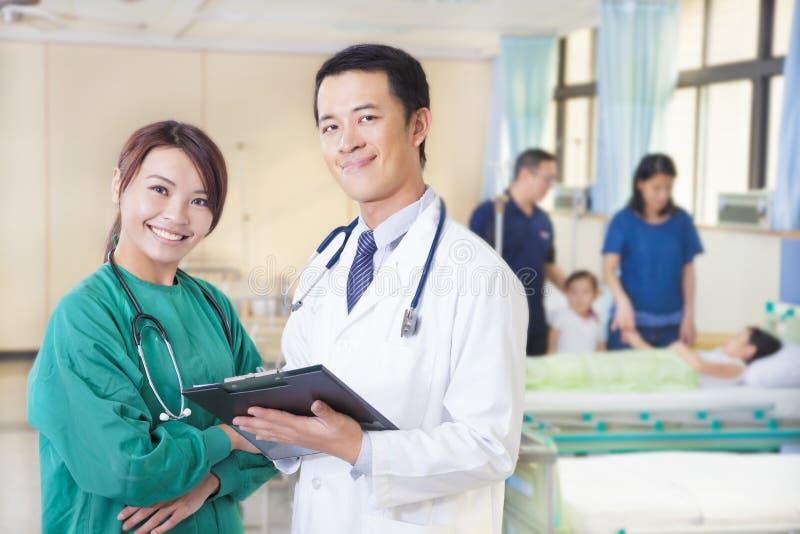 Lächelnder Doktor und Assistent mit Patienten lizenzfreie stockfotos
