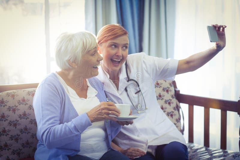 Lächelnder Doktor und Patient, die ein selfie nehmen stockbild