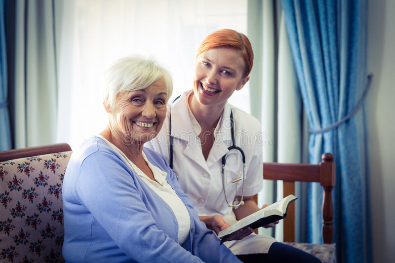 Lächelnder Doktor, welche älterer Frau hilft, ein Buch zu lesen lizenzfreie stockbilder