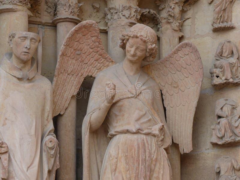 Lächelnder Engel mit dem täuschenden Lächeln, das eine Faust gibt, pumpen auf den Eingang zu Kathedrale Notre-Dame-Des Reims in F stockfotografie