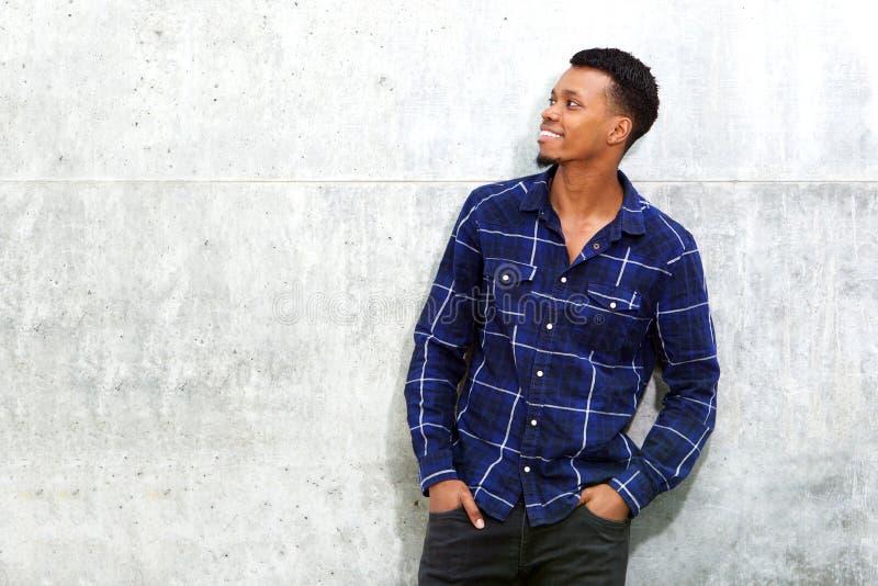 Lächelnder entspannter Afroamerikanermann, der gegen Wand steht lizenzfreie stockfotografie