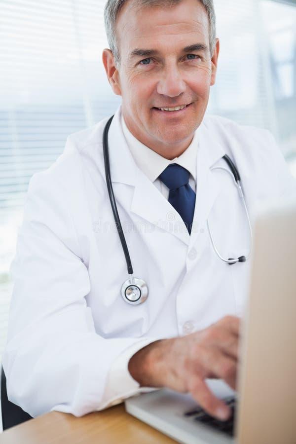 Lächelnder erfahrener Doktor, der auf seinem Laptop schreibt stockfoto