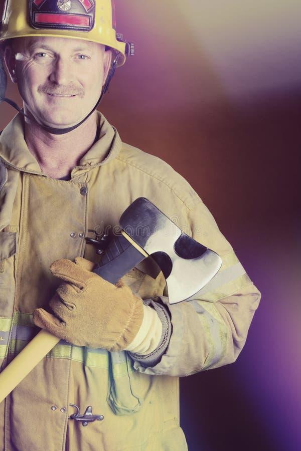 Lächelnder Feuerwehrmann Holding Axe stockfotos