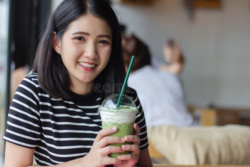 Lächelnder Frau trinkender matcha grüner Tee Latte morgens an der Kaffeestube Hübsches asiatisches Mädchen des Porträts, das here stockbild