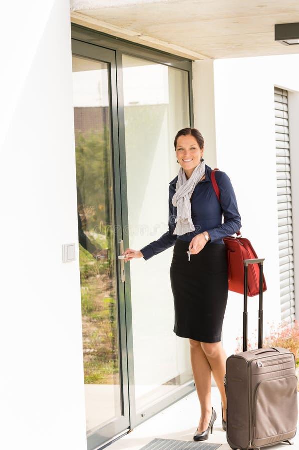Lächelnder Frauengeschäfts-Flugbegleiter, der nach Hause ankommt stockfotografie