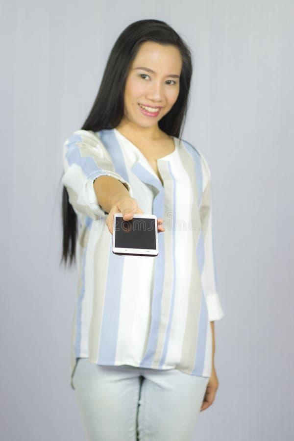 Lächelnder Frauenholdinghandy, geben Ihnen ein intelligentes Telefon Getrennt auf grauem Hintergrund stockfotos