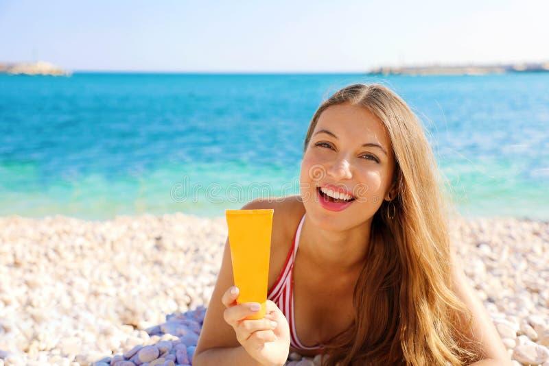 Lächelnder Frauenholdingsonnencreme-Rohrschutz, der auf Kieselstrand liegt Lichtschutzmädchen, das Sonnenschutzmittel im Plastikb lizenzfreie stockbilder