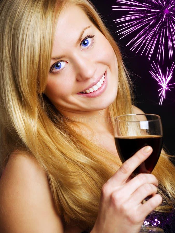 Lächelnder Frauenholdingwein und Feiern lizenzfreie stockfotografie