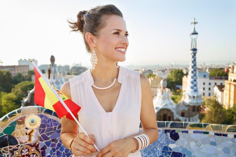 Lächelnder Frauentourist mit Spanien-Flagge im Park Guell, Barcelona stockfoto