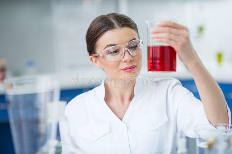 Lächelnder Frauenwissenschaftler in der schützenden Arbeitskleidung, die Flasche mit Reagens hält stockfotos