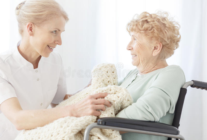 Lächelnder Freiwilliger bedeckt ältere Frau lizenzfreie stockfotografie