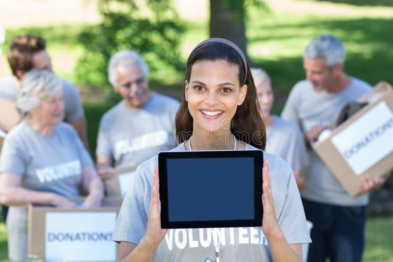 Lächelnder freiwilliger Brunette, der Tabletten-PC-Schirm zeigt stockbild