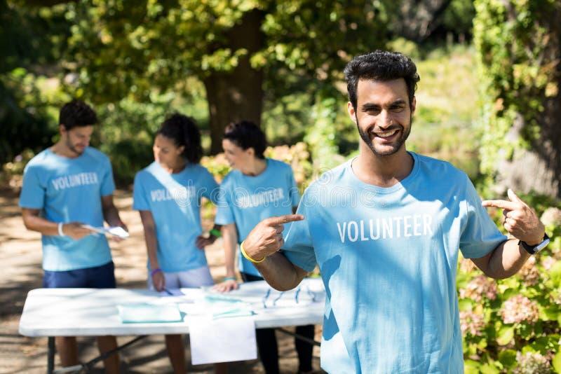 Lächelnder Freiwilliger, der auf sein T-Shirt zeigt lizenzfreies stockbild