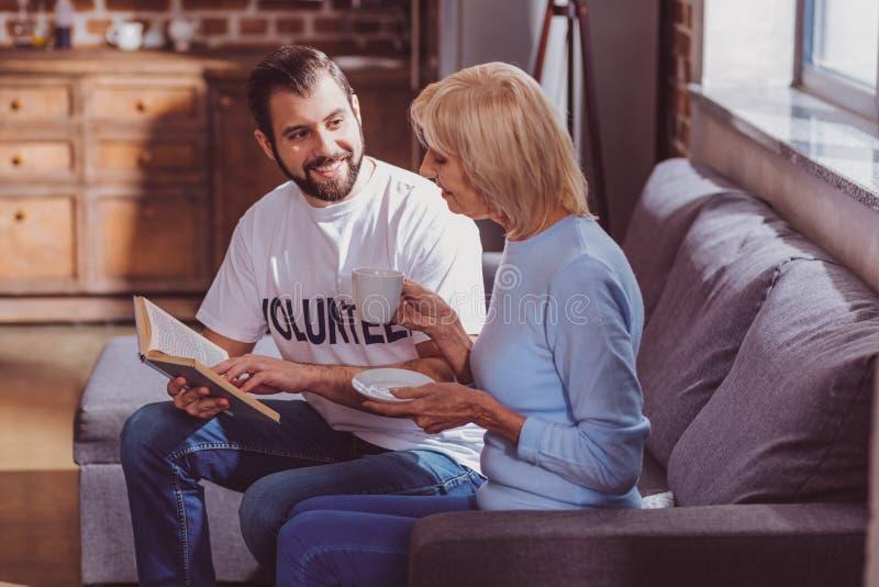 Lächelnder Freiwilliger, der ein Buch für eine Frau liest lizenzfreie stockbilder