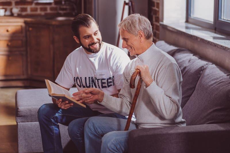 Lächelnder Freiwilliger, der ein Buch für einen Pensionär liest stockbild
