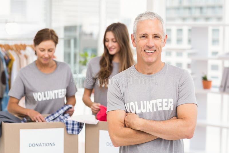 Lächelnder Freiwilliger mit den Armen gekreuzt lizenzfreies stockbild