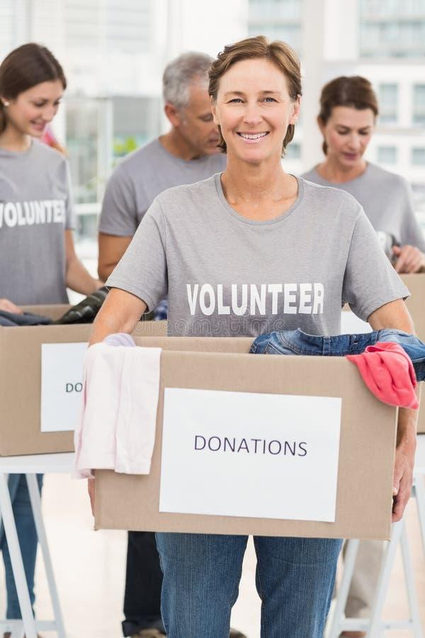 Lächelnder freiwilliger tragender Spendenkasten der Frau stockfotografie