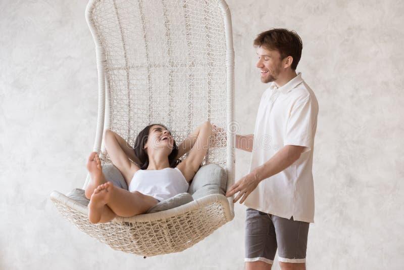 Lächelnder Freund schaukeln aufgeregte Freundin in hängendem Stuhl stockfotos