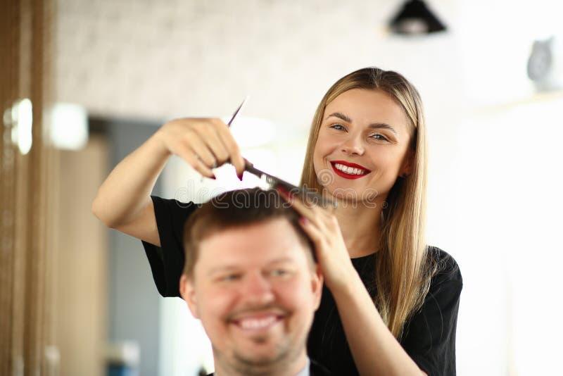 Lächelnder Friseur Combing Hair des männlichen Kunden lizenzfreies stockbild