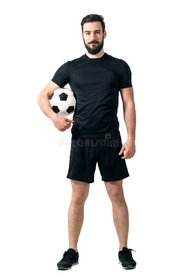 Lächelnder Fußball oder futsal Spieler, welche die schwarze Sportkleidung hält Ball unter seinem Arm betrachtet Kamera trägt stockfotos