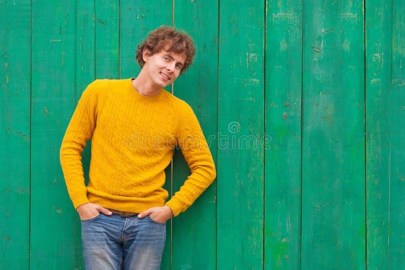 Lächelnder gelockter Mann in der gelben Strickjacke auf grünem hölzernem Hintergrund lizenzfreies stockbild