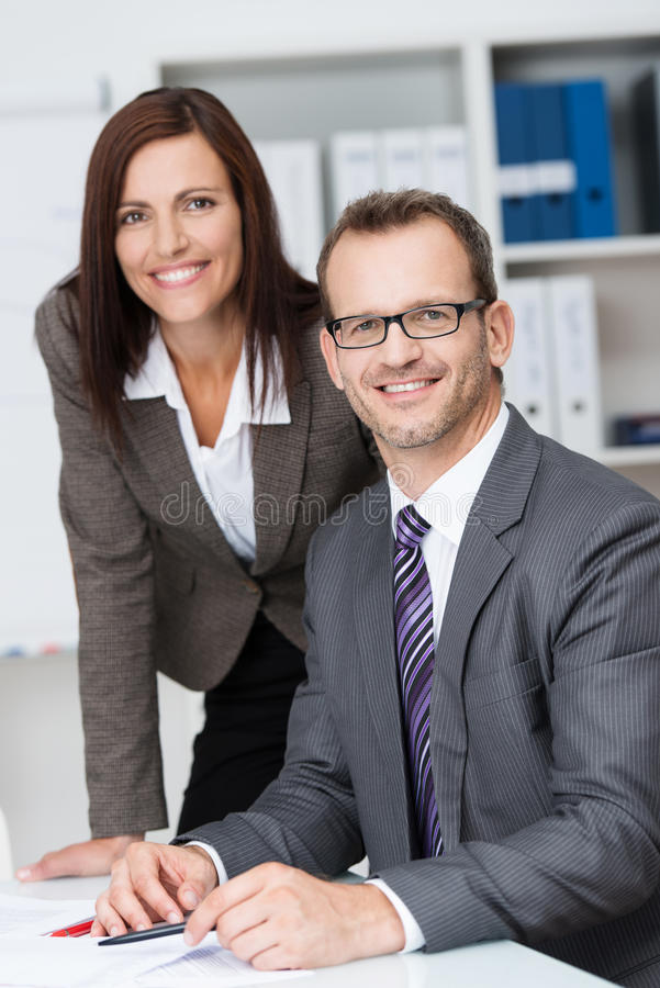 Lächelnder Geschäftsführer mit seinem Sekretär lizenzfreies stockbild