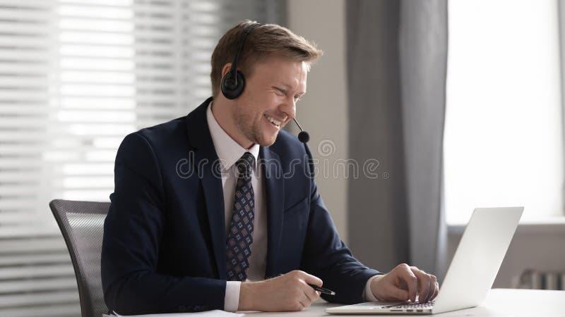 Lächelnder Geschäftsmann das drahtlose Kopfhörervideo tragen, welches das Betrachten des Laptops nennt lizenzfreie stockbilder