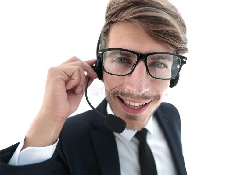 Lächelnder Geschäftsmann, der auf Kopfhörer gegen ein weißes backgroun spricht stockbild