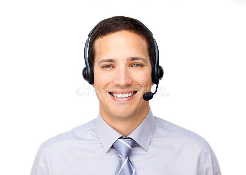 Lächelnder Geschäftsmann, der auf Kopfhörer spricht stockfoto