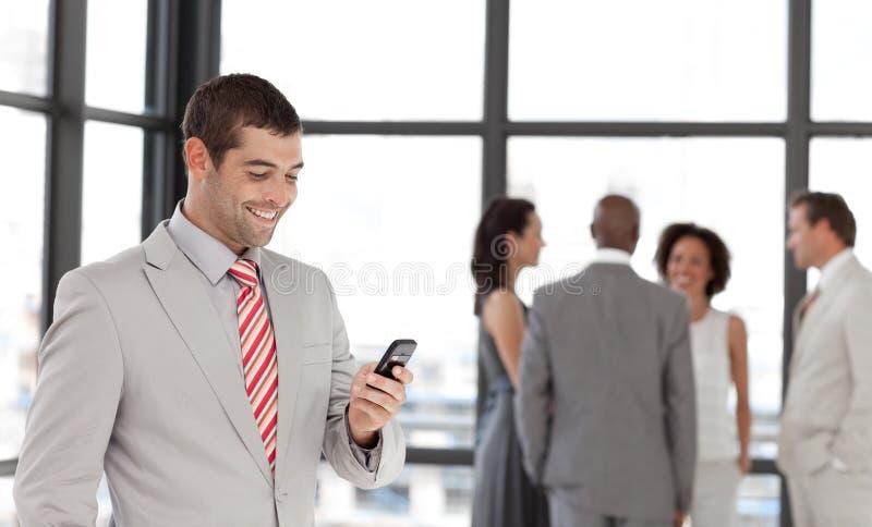 Lächelnder Geschäftsmann, der eine Textmeldung sendet stockbilder