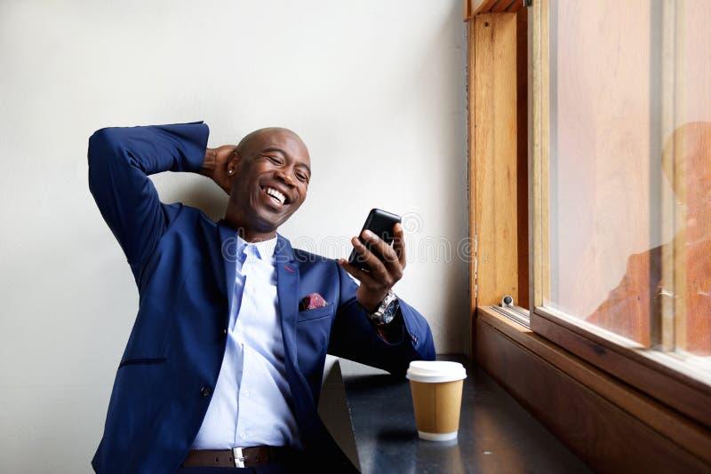 Lächelnder Geschäftsmann, der an einem Café betrachtet Handy sitzt stockbilder