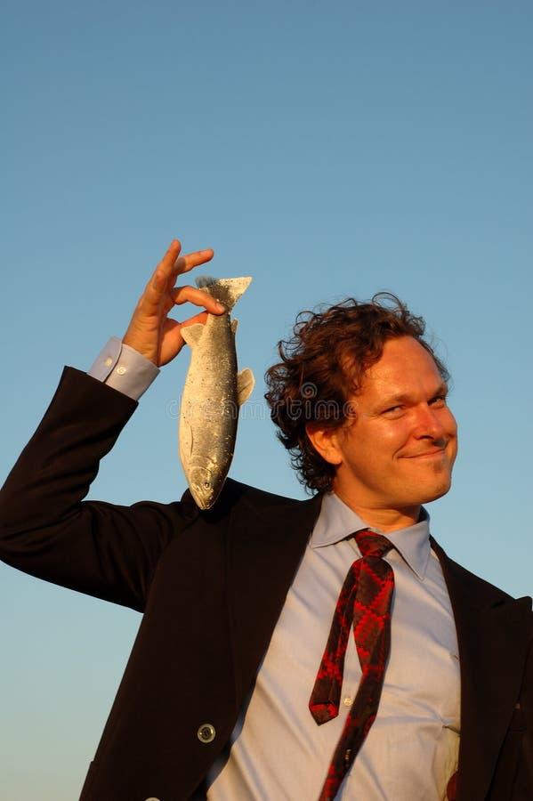 Lächelnder Geschäftsmann, der einen Fisch anhält lizenzfreies stockbild