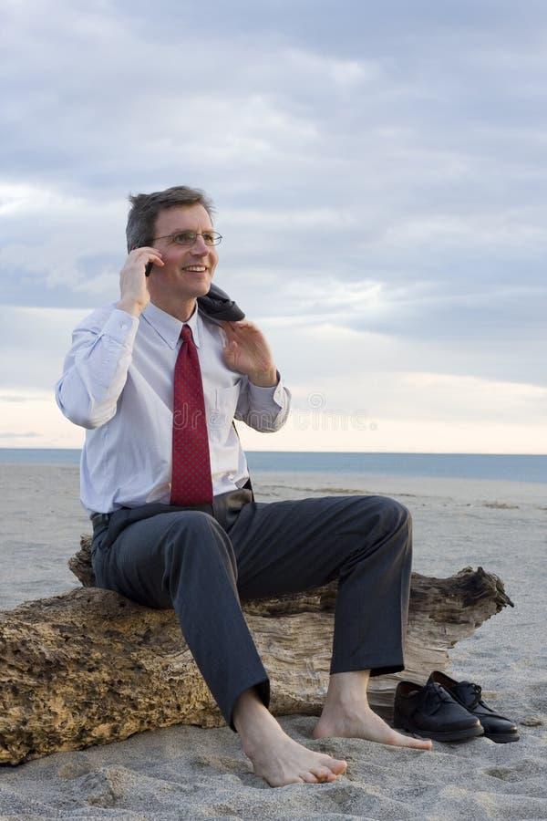 Lächelnder Geschäftsmann, der einen Telefonaufruf auf einem Strand bildet lizenzfreie stockfotografie