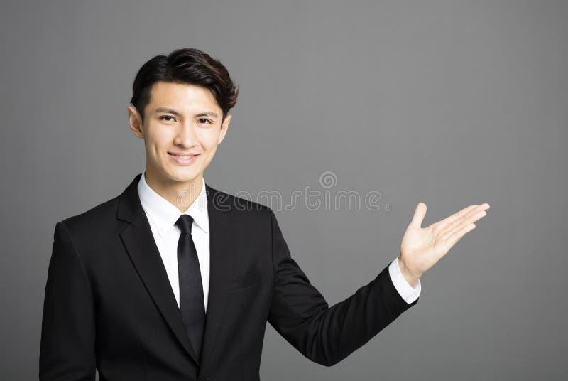 Lächelnder Geschäftsmann, der etwas vorstellt lizenzfreies stockbild