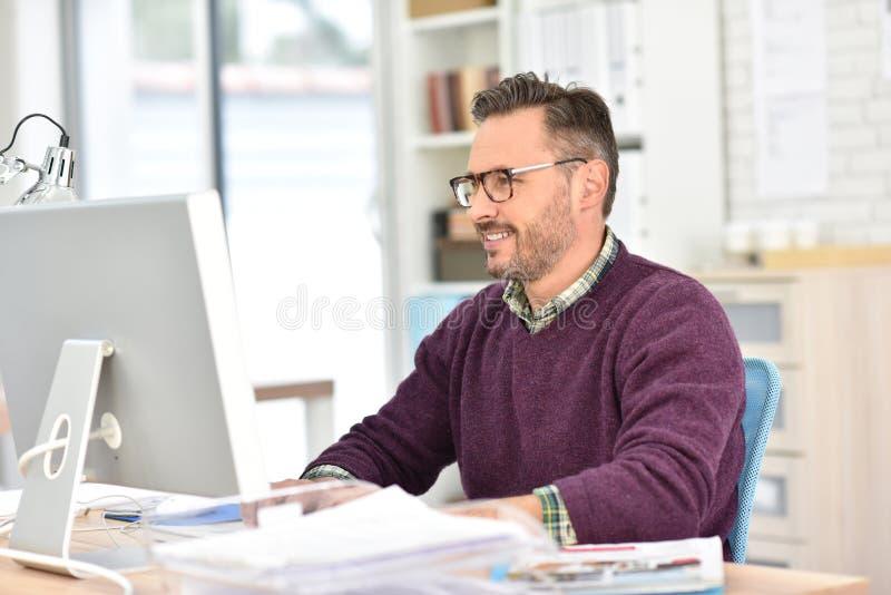 Lächelnder Geschäftsmann, der im Büro arbeitet lizenzfreie stockfotos