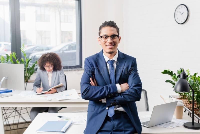 Lächelnder Geschäftsmann, der im Büro mit seinem weiblichen Mitarbeiter durch Tabelle steht stockfotos