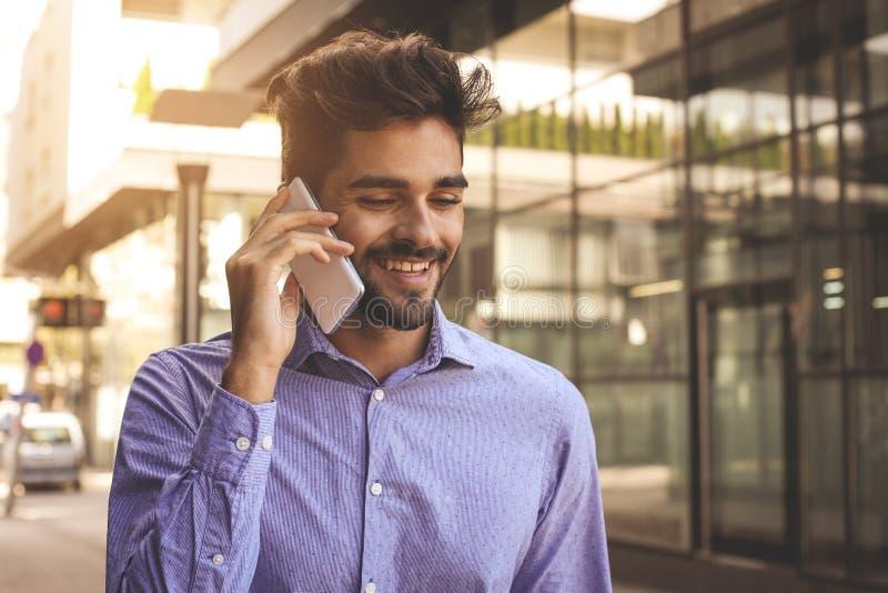 Lächelnder Geschäftsmann, der am intelligenten Telefon auf Stadtstraße spricht Mann lizenzfreies stockfoto