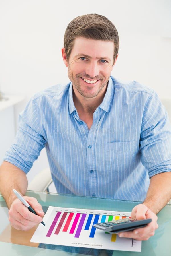 Lächelnder Geschäftsmann, der an messendem Diagramm an seinem Schreibtisch arbeitet stock abbildung