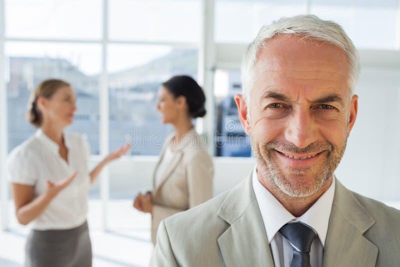 Lächelnder Geschäftsmann, der vor Kollegen steht lizenzfreie stockbilder