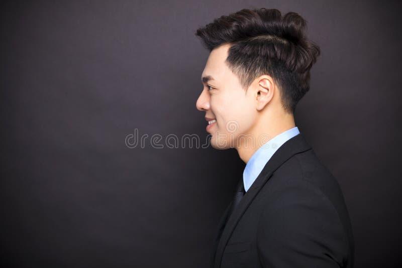 Lächelnder Geschäftsmann, der vor schwarzem Hintergrund steht stockfotografie