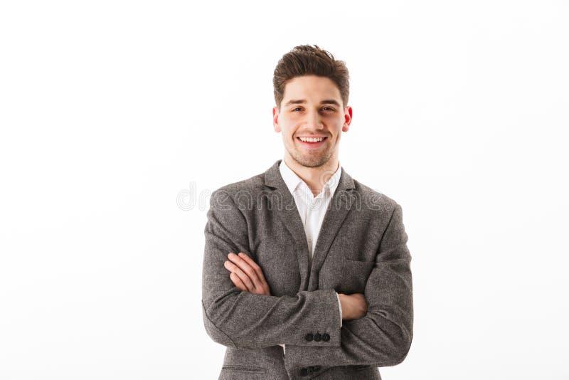 Lächelnder Geschäftsmann mit den gekreuzten Armen, welche die Kamera betrachten stockfotos