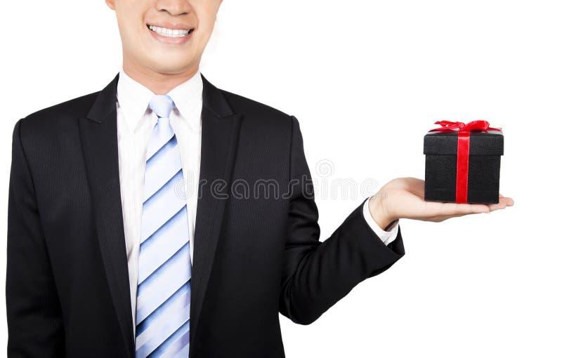 Lächelnder Geschäftsmann mit einem Geschenk lizenzfreie stockfotografie